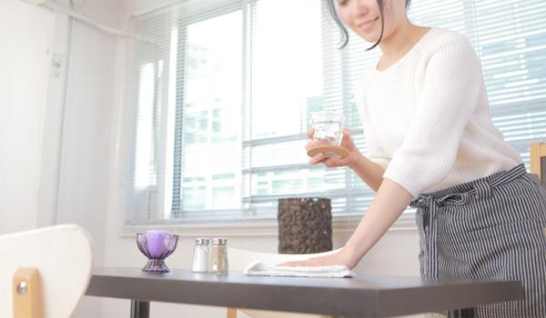 テーブルを拭く女性店員